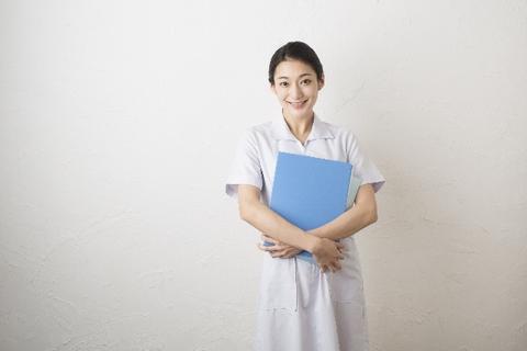 青いバインダーを持って微笑む看護婦