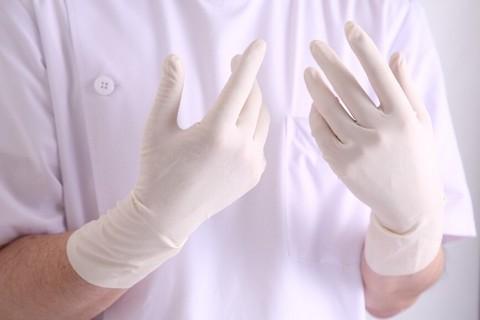 手術をするための白い手袋をつけたお医者さん