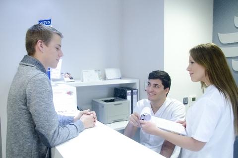 病院の受付で患者の話を聞いているスタッフ二名