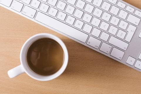 パソコンのキーボード前に置いてあるアツアツのカフェオレ