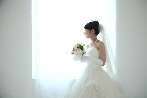 ブーケを持って窓から外を眺める花嫁