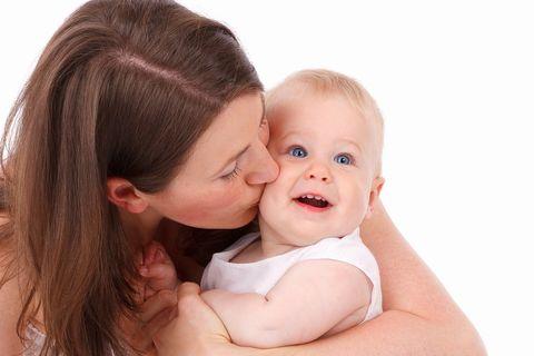 赤ちゃんを左腕に抱いてほっぺにチューしているお母さん