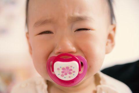 歯固めを加えて泣いている赤ちゃん