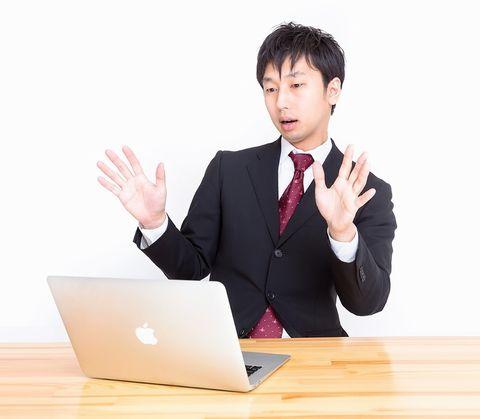 ノートパソコンを見てびっくりしているサラリーマン