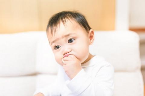 左手を口にくわえている赤ちゃん