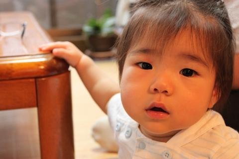 つかまり立ちを始めた1歳の赤ちゃん